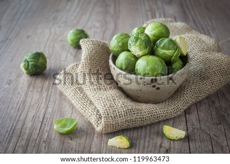 Bunch of fresh Bruxelles sprouts in a cup on wooden background - stock photo
