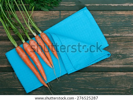 Bunch of fresh carrots with leaves on a rustic background - stock photo