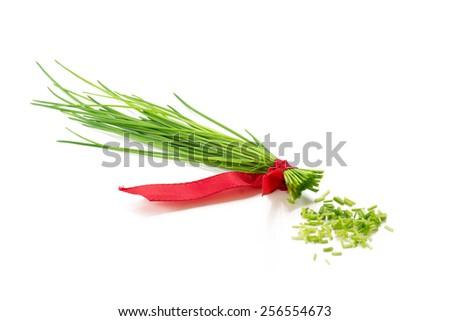 bunch of fresh chives with a red ribbon isolated on a white background - stock photo