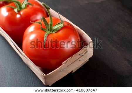 Bunch of fresh delicious red organic tomatoes in rustic basket on grey old kitchen table, horizontal image - stock photo