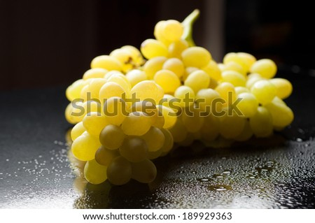 bunch of fresh grapes on black glossy background - stock photo