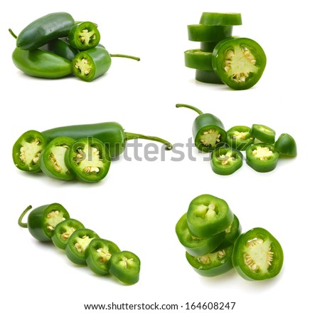 bunch of fresh green chili peppers and some cut pieces on a white background  - stock photo