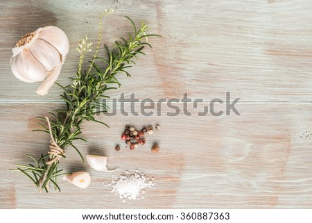 Bunch of fresh of garden rosemary on wooden table, rustic style, fresh organic herbs with salt, chili and garlic. Top view with copy space - stock photo