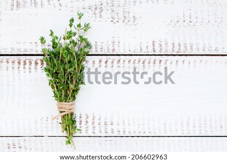 bunch of fresh organic thyme on a white wooden background - stock photo