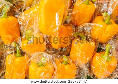 Bunch of fresh plastic wrapped yellow bell peppers - stock photo
