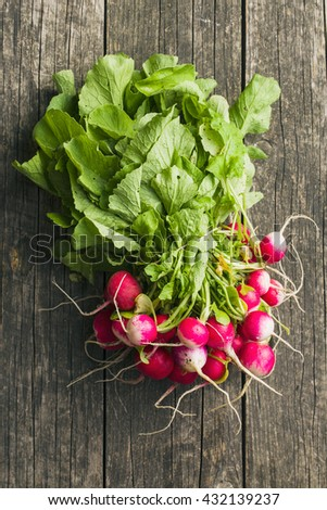 Bunch of fresh radishes. Fresh radishes on old wooden table. Top view. - stock photo