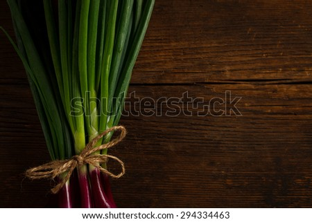 Bunch of fresh spring onions tied with a rope, rustic wooden background - stock photo
