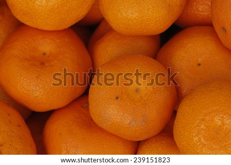Bunch of fresh tangerines oranges in market box, top view. Tangerines as the background. Big bunch of ripe tangerines. - stock photo