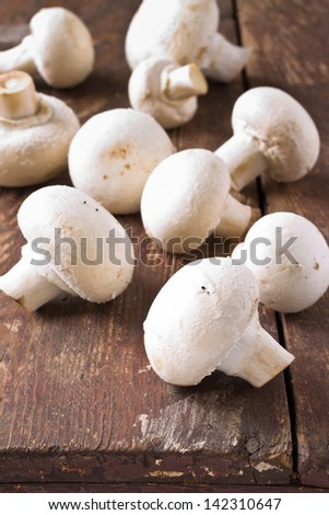 Bunch of fresh white mushrooms on a wooden background - stock photo