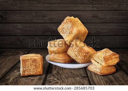 Bunch of freshly baked Zu-Zu, a Serbian Small Square Shaped Croissant Puff Pastries, sprinkled with Sesame Seeds, offered on small White Porcelain Plate, set on Rustic Garden Table Surface. - stock photo