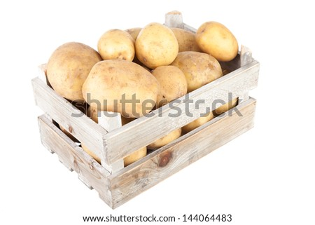 bunch of freshly harvested potatoes in a wooden crate viewed from above - stock photo