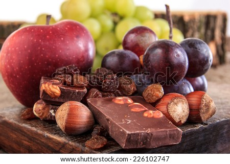 Bunch of fruit apples and grapes with nuts chocolate , Chocolate with nuts raisins apple and grapes on wooden background - stock photo
