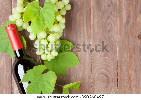 Bunch of grapes and red wine bottle on wooden table background with copy space - stock photo