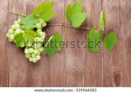 Bunch of grapes and vine on wooden table background with copy space - stock photo