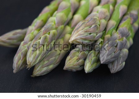 Bunch of green asparagus on dark back ground - stock photo