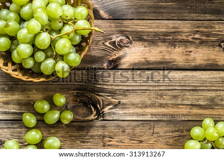 Bunch of green grapes in the basket, fruits of autumn, a symbol of abundance on rustic wood background with copy space, top view, close-up. - stock photo