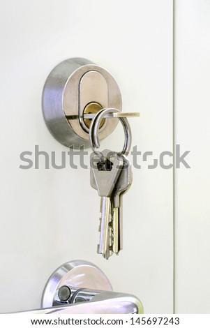 Bunch of keys hanging at the door lock. - stock photo