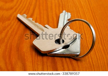 Bunch of keys on a wooden texture. - stock photo