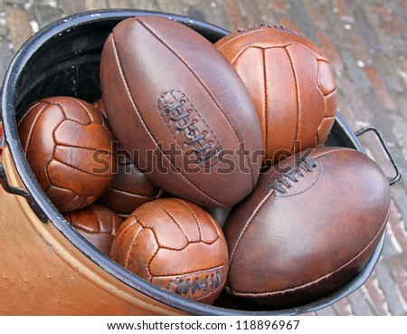 Bunch of leather sport balls in metal container - stock photo