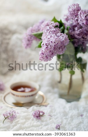 Bunch of lilac flowers and a cop of tea on tender textile background - stock photo
