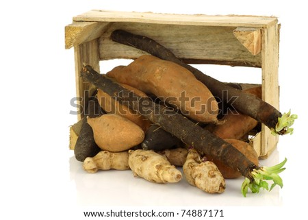 bunch of mixed vegetables coming out of a wooden box on a white background - stock photo