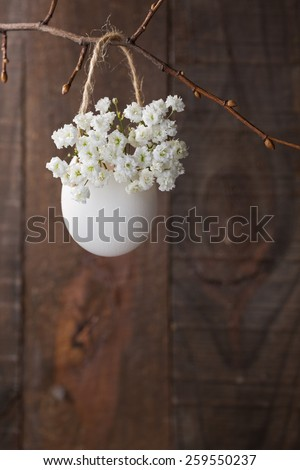 Bunch of of white baby's breath flowers (gypsophila) in egg shell on the brown wooden plank. Shallow depth of field, focus on near flowers. Easter decor - stock photo