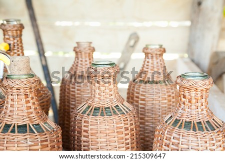 Bunch of old wine bottles with wickerwork cover  - stock photo