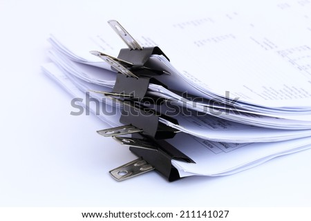 bunch of paperwork with black paper clippers isolated for business organization study neat and tidy  - stock photo