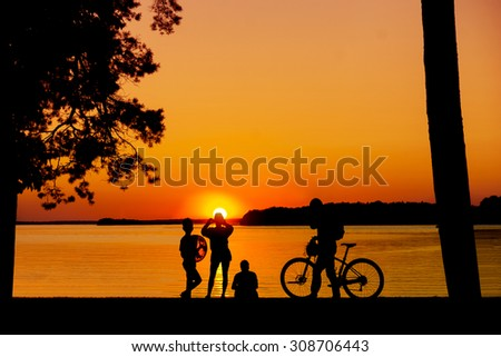 Bunch of people enjoying sunset over water and taking photos with mobile phone - stock photo