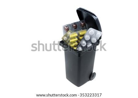Bunch of pills in the trash bin - stock photo