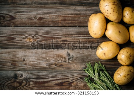 Bunch of potatoes on wooden background close up, space for text - stock photo