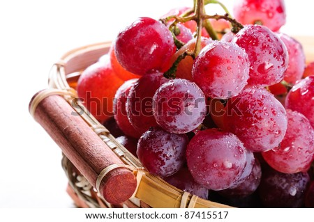 Bunch of red grapes in a basket on a white background. - stock photo