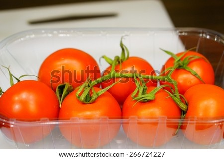 Bunch of red tomatoes in plastic box - stock photo