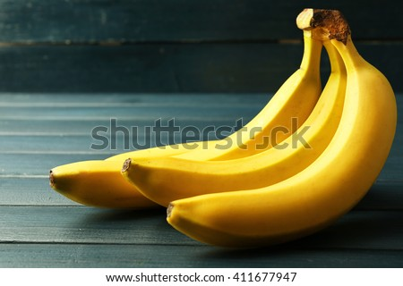 Bunch of ripe bananas on dark wooden background - stock photo