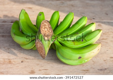 Bunch of ripe bananas on wooden table - stock photo