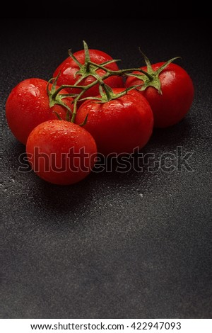 bunch of ripe cherry tomatoes on a dark marble background, water drops on red delicious tomatoes. copy space - stock photo