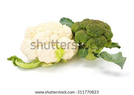 Bunch of ripe fresh broccoli cabbage and cauliflower crop on leaves - stock photo