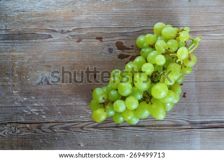 Bunch of ripe tasty sweet green grapes on old wooden background. Top view. - stock photo