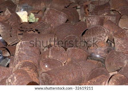 Bunch of rusted cans laying on the ground - stock photo