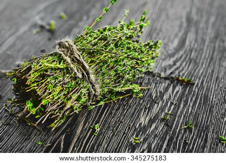Bunch of thyme tied by a rope on a dark wood background - stock photo