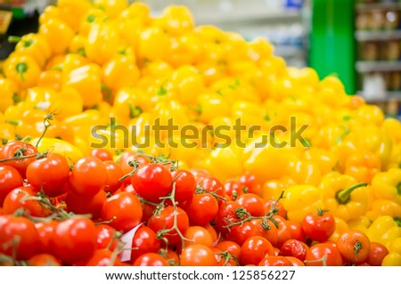 Bunch of tomatoes and paprika peppers on back in supermarket - stock photo