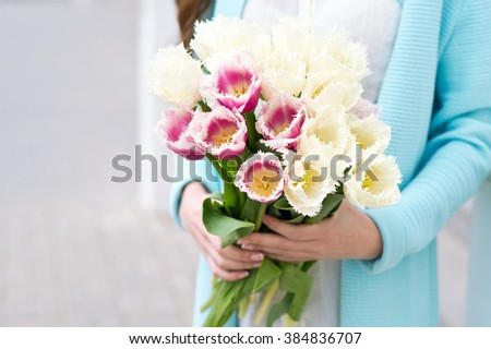 Bunch of tulips in woman's hands  - stock photo