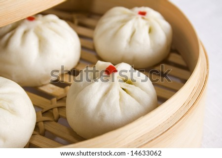 Bunch of vegetarian stuffed dumplings on a bamboo steamer. Main focus on the dumpling at the front. - stock photo