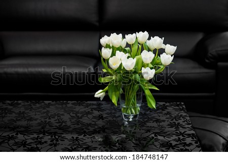 Bunch of white tulips on the glass coffee table in room with black design - stock photo