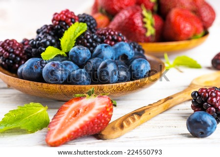 bunch of wild berries and mint on a wooden board - stock photo