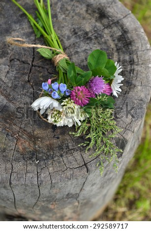 Bunch of wildflowers on old wooden stub, rural summer still life - stock photo