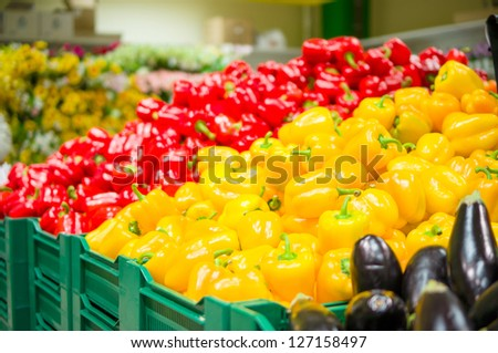 Bunch of yellow and red paprika peppers on boxes in supermarket - stock photo