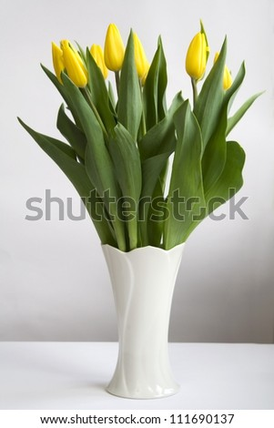 Bunch of yellow tulips in white vase - stock photo