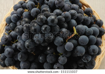 Bunches of black grapes in a basket - stock photo