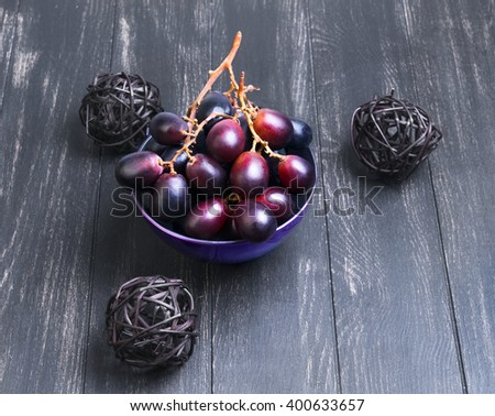 Bunches of grapes Crimson large in purple mask on a black wooden background in rustic style - stock photo